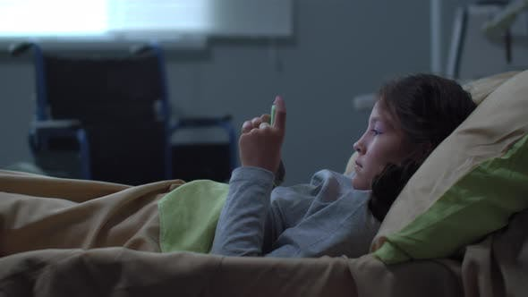 Thumbnail for Little Girl Lie with Phone in the Bed in the Hospital