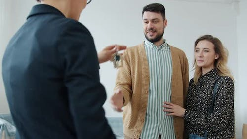 Joyful Couple Shaking Hands with Realtor Getting House Key Talking Discussing Deal