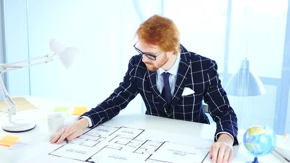 Thumbnail for Redhead Architectural Engineer Opening Blueprint on Desk in Office