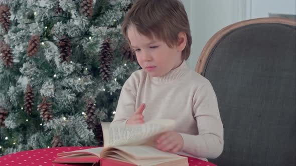 Thumbnail for Serious Little Boy Exploring a Book on Christmas Eve