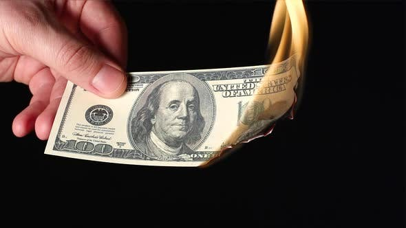 Thumbnail for A human hand holds one hundred dollars flaming on a black background
