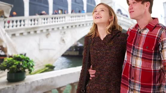 Cheerful millennial couple taking leisurely stroll by the Grand Canal