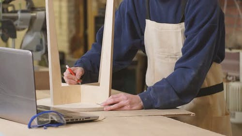 Hardworking Woodworker Marks with a Pencil