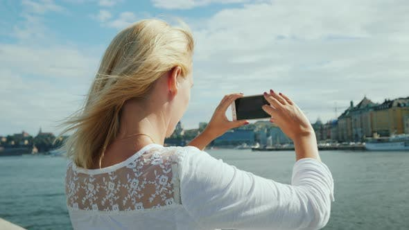 Cover Image for A Young Woman Photographs a Beautiful View of the City of Stockholm. Travel in Sweden