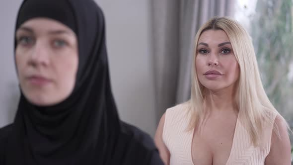 Thumbnail for Change of Focus From Caucasian Blond Woman To Face of Muslim Lady in Hijab Looking at Camera. Modern