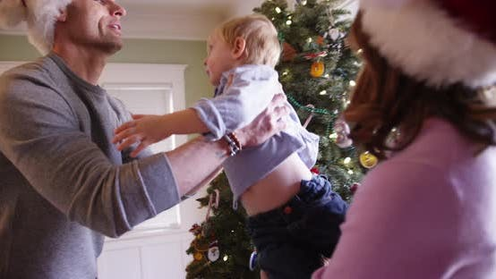 Thumbnail for Good-looking parents and adorable two kids looking at a x-mas tree