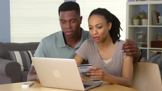 Thumbnail for Smiling young black couple using credit card to make online purchase