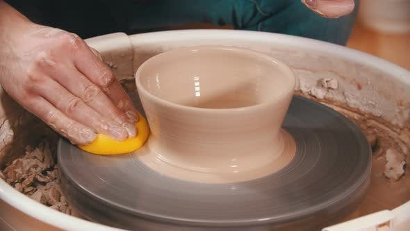 Thumbnail for Pottery - the Master Is Wiping the Potter's Wheel with a Yellow Sponge
