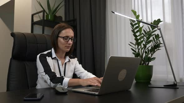 Thumbnail for Young brunette businesswoman in eyeglasses works on laptop computer in her modern home workplace