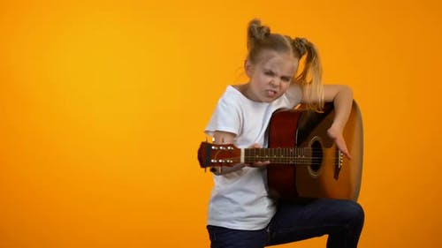 Funny Preteen Girl Pretending to Play Guitar Dreaming to Become Famous Rock Star