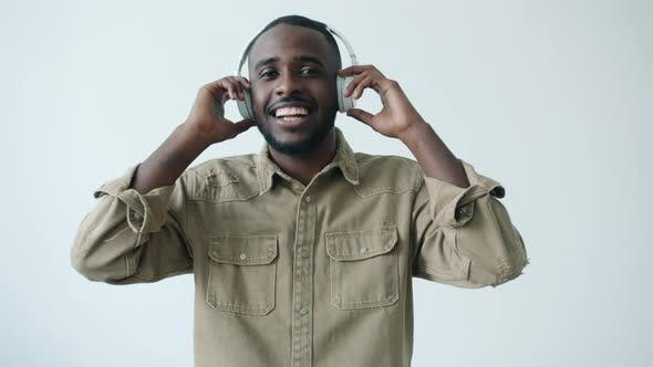 Slow Motion Portrait of African American Student Wearing Headphones Dancing on White Background