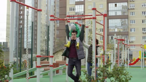 Thumbnail for Man Doing Pull-Ups with Son on Shoulders