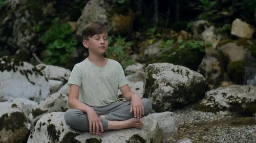 Peaceful Boy meditating sitting among the stones by the mountain river