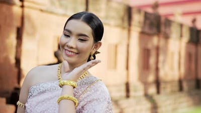 Thai woman in traditional costume is dancing