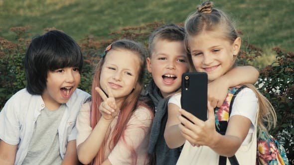 Cover Image for Cool kids taking selfie smiling and making victory gesture.