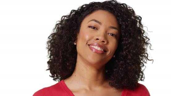 Close-up of pretty African woman with curly hair laughing at camera in studio