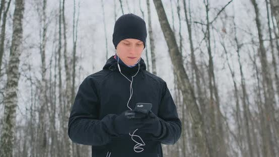 Thumbnail for A Young Man in a Black Hammer in the Winter Is Preparing To Jog in the Park