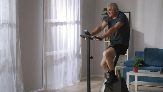 Sporty Middle Aged Man Is Training with Stationary Bicycle at Home Medium Shot in Living Room