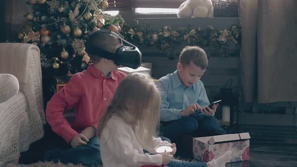 Little Boys Play with Modern Gadgets and Girl Opens Present