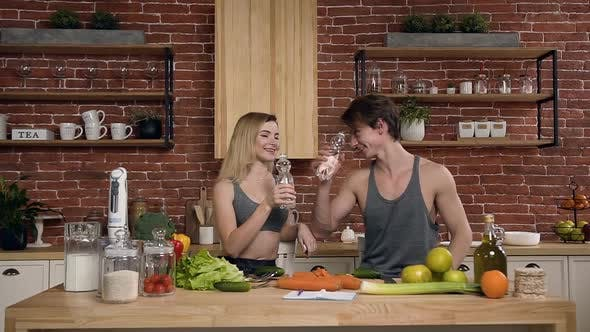 Thumbnail for Cute sport couple drinking water in the kitchen.