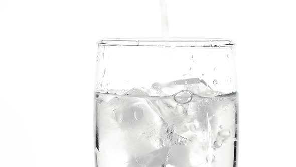 Thumbnail for Pouring still water in glass full of ice cubes over white background