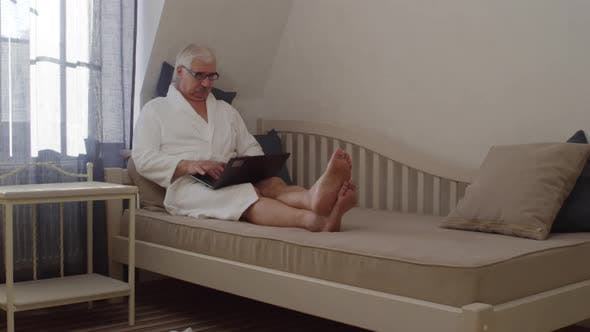 Thumbnail for Mature Grey-Haired Caucasian Man Resting in Hotel with Laptop