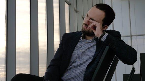 Thumbnail for Tired sleepy man at the airport waiting.