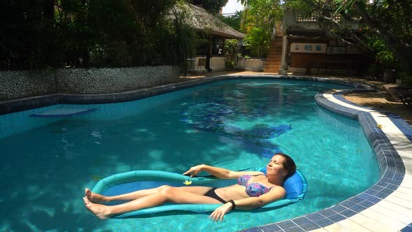 Young Woman Lying on Water Mattress in the Pool on a Sunny Day