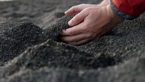 Thumbnail for Slow Motion of Men's Hands Take the Black Volcanic Sand, Pouring Through the Fingers at Reynisfjara
