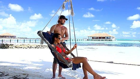 Thumbnail for Glückliches Paar Entspannen in Swing am exotischen Strand