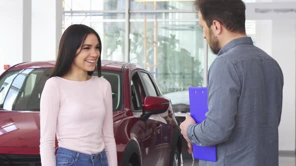 Thumbnail for Gorgeous Happy Woman Shaking Hands with Car Dealer after Receiving Car Keys
