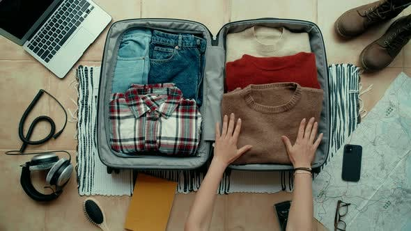 Woman Packs Suitcase for Travel or Adventure