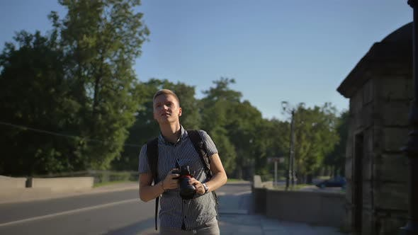 Thumbnail for A Tourist Standing Near the Road and Looking for Good Camera Angles for Taking Great Shot
