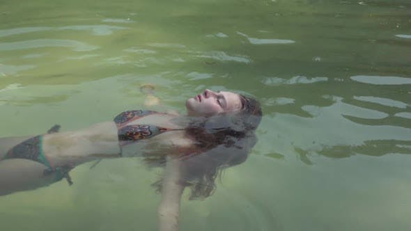 Cover Image for Attractive Girl Lying in the Clean Water on Her Back, Relaxing
