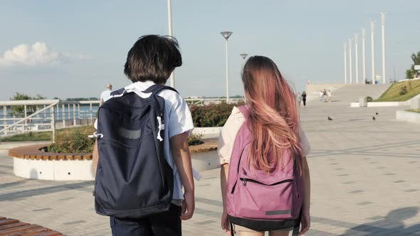 Two Classmates Walking with Backpacks.