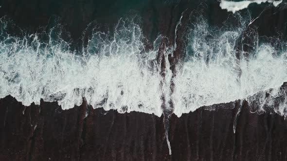 Wellen brechen über ein flaches Riff