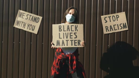"Thumbnail for Caucasian woman in protective face mask with poster ""Black lives matter"""