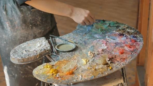 Thumbnail for Künstler in Schmutzige Schürze mischt Ölfarben auf Palette im Studio