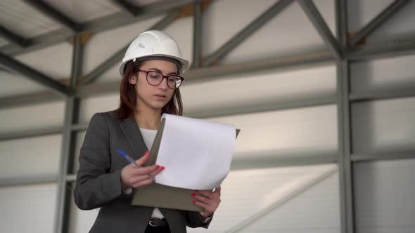 Thumbnail for Young Woman in a Helmet with Documents at a Construction Site. The Boss Woman in a Suit Keeps
