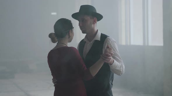 Thumbnail for Portrait Man in Fedora Hat, Classical Suits and Woman in Style Cloth Dancing in Abandoned Building