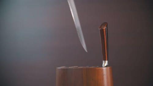 Eine Person, die das Messer an einen hölzernen Messerhalter setzt