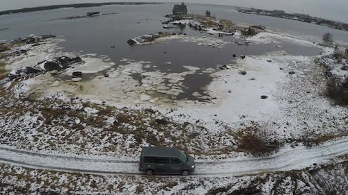 Flying over car driving by the waterside in winter