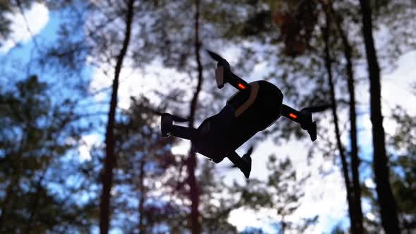 Thumbnail for Silhouette of Drone with Camera Hovers in Air on Backdrop of Sunset. Slow Motion