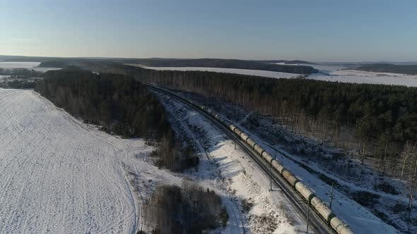 Freight train of oil tank cars travels by rail to leaves into the distance