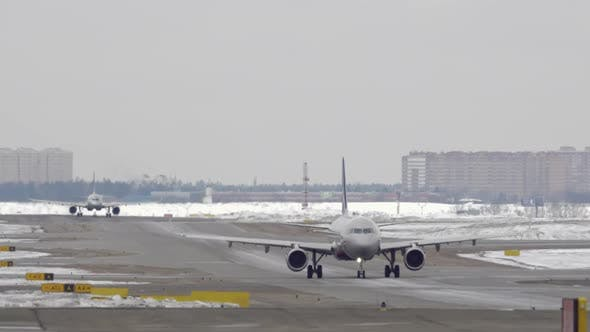 Thumbnail for Planes Taxiing on the Snowy Runway