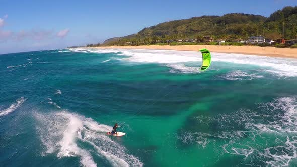 Aerial view of a man kitesurfing in Hawaii.