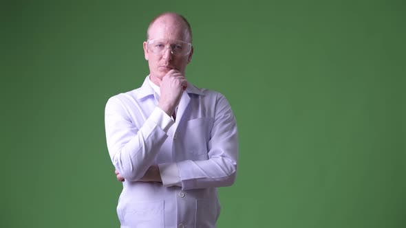 Thumbnail for Mature Bald Man Doctor with Protective Glasses Thinking