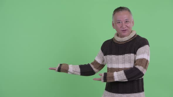 Thumbnail for Happy Mature Japanese Man Talking While Showing Something
