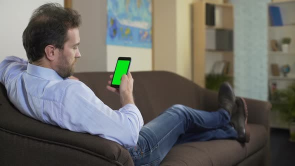 Thumbnail for Relaxed Person Sitting on Sofa and Searching Hotel for Vacation on Smartphone