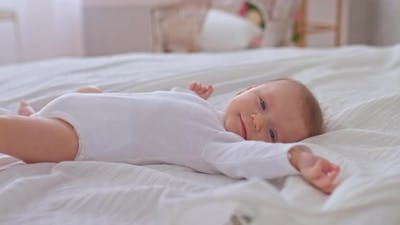 Newborn Baby Lies on the Bed and Smiles